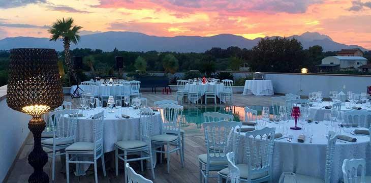 terrazza al tramonto con tavoli imbanditi